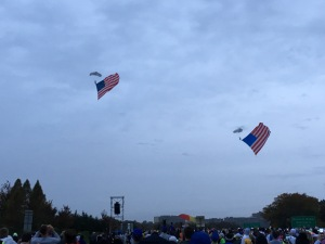 The parachute performers landing at the front of the corrals.